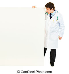 Full length portrait of medical doctor looking at blank billboard isolated on white