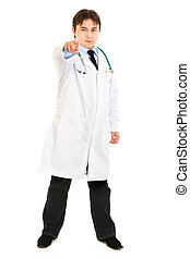 Full length portrait of confident medical doctor pointing finger at you isolated on white