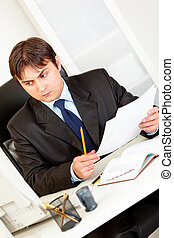 Concentrated businessman with documents sitting at office desk and looking at computer monitor
