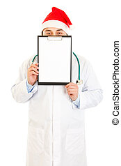 Medical doctor in Santa hat holding blank clipboard isolated...