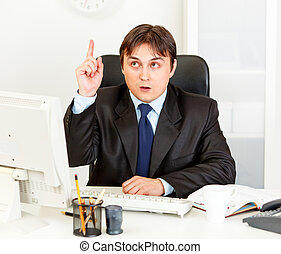 Concentrated modern businessman with rised finger sitting at...