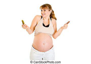 Pickles or chocolate Beautiful pregnant woman making choice...
