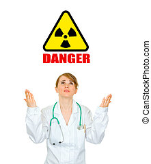 Concept- radiation danger!  Frustrated medical doctor woman looking up and  raising her hands isolated on white