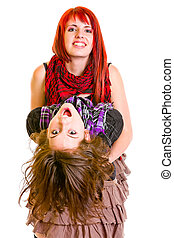 Two jaunty young girlfriends funny embracing isolated on...