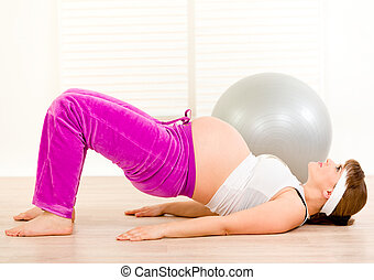 Beautiful pregnant female doing fitness exercises at living...