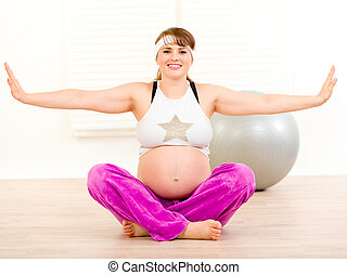 Happy beautiful pregnant woman doing pilates exercises at...
