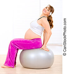 Smiling beautiful pregnant woman doing pilates exercises on...