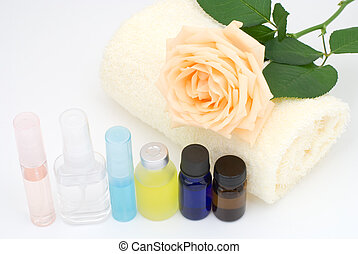 Essential oil and yellow towel with rose on white background