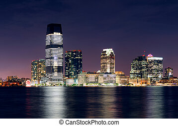 Jersey City skyline with skyscrapers at night over Hudson...
