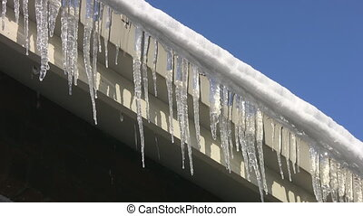 Rooftop Icicles. - Icicles dripping from the edge of a roof.