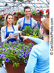 Woman buying flowers  at a flower shop. Gardening.
