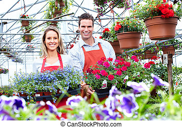 Florists couple working at flower shop. - Florists couple...
