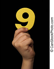 Children hand holding the number Nine