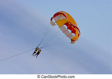Parachute with soaring people on a background of the blue...