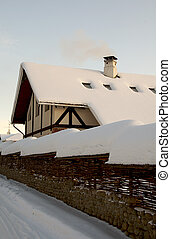 Winter country building under the snow with smoke from the...