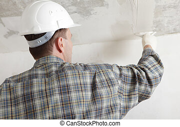 Construction worker plastering the ceiling - Construction...