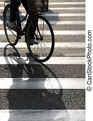 Cyclist on pedestrian crossing - Cyclist with shadow on...
