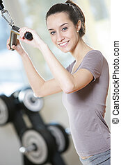 smiling young woman doing on a weight machine at the health...