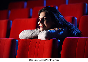 funny movie: portrait of a pretty girl in a movie theater, she leans her elbows on the back row of chairs in front of her, totally relaxed