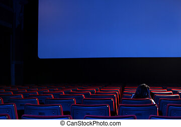 the end: youn woman alone sitting in a empty movie...