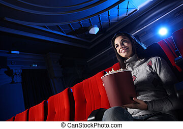 a pretty young woman sitting in an empty theater, she eats popcorn and smiles,behind her you see the blue light beam of the projector.