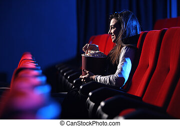 funny movie: portrait of a pretty young woman, eats popcorn and smiles, side view