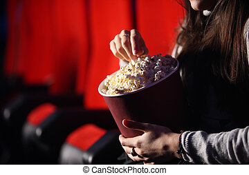 close up of the hands of a girl in a movie theater, she eats...