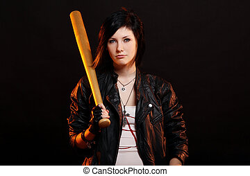 Young punk girl with baseball bat over black background