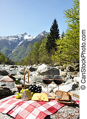 Red wine, cheese and grapes served at a picnic Verzasca...