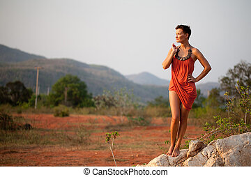 Beautiful  woman standing on a rock