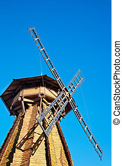 Old wooden mill against the blue sky