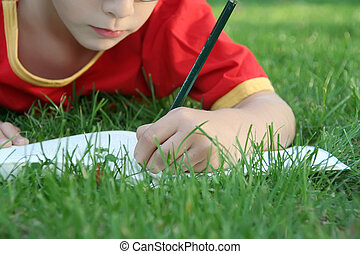 Boy writing in the park