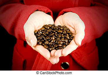 love coffee, woman holding coffee beans with hands in love...