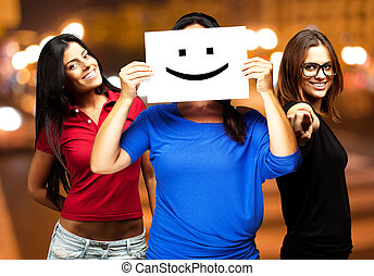 young friends holding a happy emoticon at city by night