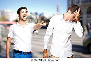 young man pointing a guy and joking at city