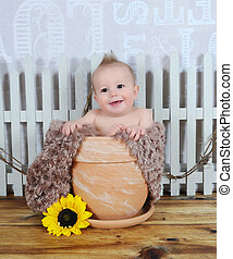 adorable baby boy sitting in clay flower pot