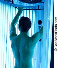 solarium - young man closeup at tanning solarium light on