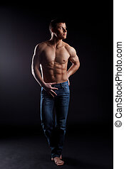 man with naked torso in jeans posing from dark