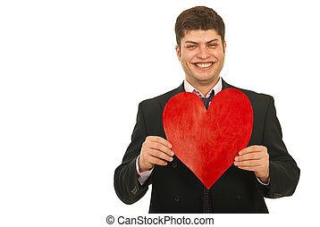Laughing business man holding heart shape isolated on white...