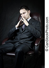 Young adult handsome businessman sitting on leather chair...