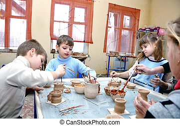 children shaping clay in pottery studio - group of children...
