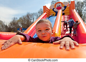 Boy inflatable slide - Smiling little boy playing on...