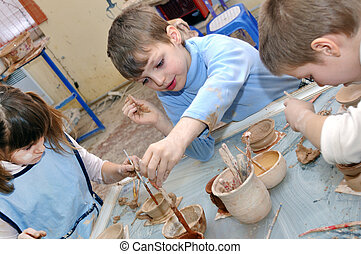 group of hildren shaping clay in pottery studio - group of...