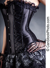 Close-up shot of elegant woman in black corset, studio shot