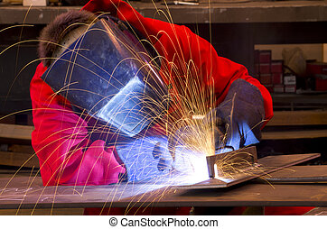 Welder in red overalls creates sparks. - Welder in workshop...