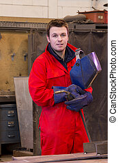 Friendly welder looks at camera - Welder in workshop...