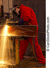 Welder in red overalls cuts metal. - Welder in workshop...