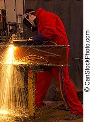Welder in red overalls cuts metal.