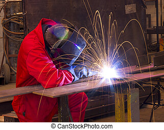 Welder bends to cut metal beam with orange sparks - Welder...
