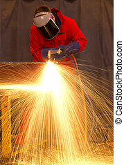 Welder in red creates huge  orange sparks